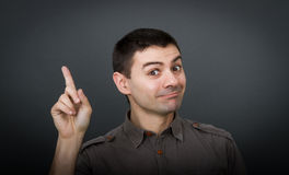 Man indicated with finger. Expressions for a man, gray background royalty free stock photography