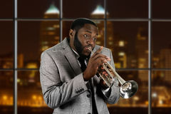 Expressive afro guy playing trumpet. Stock Images