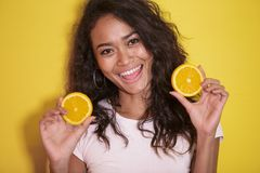Expressive asian woman with slices of fresh lemon. Close up portrait of expressive asian woman with slices of fresh lemon on yellow background Royalty Free Stock Images