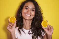 Expressive asian woman with slices of fresh lemon. Close up portrait of expressive asian woman with slices of fresh lemon on yellow background Royalty Free Stock Image