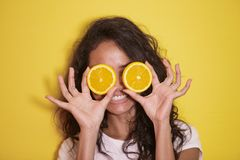 Expressive asian woman with slices of fresh lemon. Close up portrait of expressive asian woman with slices of fresh lemon on yellow background Royalty Free Stock Photo