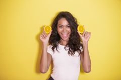 Expressive asian woman with slices of fresh lemon. Portrait of expressive asian woman with slices of fresh lemon on yellow background Stock Image