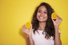 Expressive asian woman with slices of fresh lemon. Portrait of expressive asian woman with slices of fresh lemon on yellow background Royalty Free Stock Photos