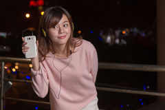 Expressive Asian woman with smart phone and yellow headphones Stock Photos