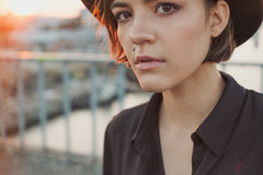 Expressive attentive look girl teenager in black hat. Urban port river background. Natural sunset light royalty free stock photos