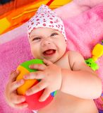 Expressive baby with ball. From above adorable expressive baby looking at camera and holding colorful ball stock photo
