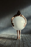 Expressive ballet dancer holding the big balloon in the studio Stock Image