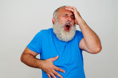 Expressive bearded man gesturing head and stomach ache Royalty Free Stock Photo