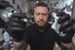 Expressive bearded tattoo artist working at his tattoo shop stock images