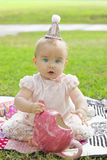 Expressive Birthday Girl. A cute smiling baby girl with expressive big blue eyes wears a birthday hat and celebrates her first birthday at a tea party in the royalty free stock photography