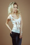 Expressive blonde girl in a white torn top Royalty Free Stock Photos
