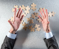 Expressive businessman hands challenging the connection of jigsaw pieces. For concept of unity and cooperation strategy, managing corporate togetherness or Stock Photo