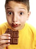 Expressive child eating chocolate Royalty Free Stock Photography