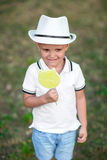 An expressive child in a hat holding candy on a garden background. Curious boy with a green lollipop. Kids with sweets. Stock Photography