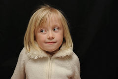 Expressive child portrait. Expressive portrait of young child with funny expression on face looking to left of photo. Confused/Uncertain expression Stock Photo