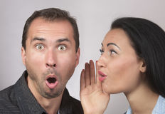 Expressive couple gossiping stock images