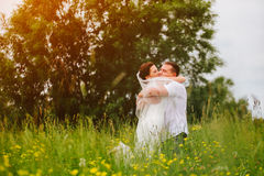 Expressive couple sincerely hugging themself on the sunset meadow Royalty Free Stock Photography