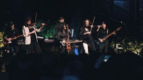 Expressive and emotional violinist girls perform on stage with a rock band stock video footage