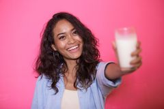 Expressive face of asian woman offering a glass of milk Stock Photo