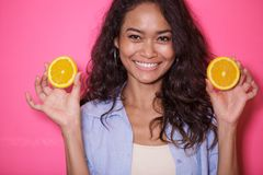 Expressive face of asian woman play with slices of lemon. Close up portrait of expressive face of asian woman play woth slices of lemon on pink background Royalty Free Stock Image