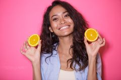 Expressive face of asian woman play with slices of lemon. Close up portrait of expressive face of asian woman play woth slices of lemon on pink background Royalty Free Stock Images