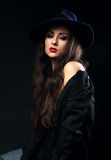 Expressive female model posing in black shirt and elegant hat wi Stock Photo