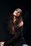 Expressive female model posing in black shirt and elegant hat wi Stock Image