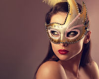 Expressive female model posing in carnival mask with red lipstick and looking vamp on empty copy space background. Closeup. Vintage portrait. Art royalty free stock image