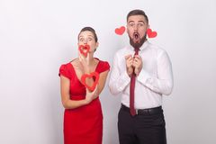 Expressive funny couple holding decorative sign love, heart symbol. Indoor, studio shot, on gray background royalty free stock photography