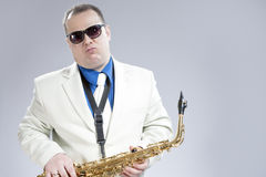 Expressive Funny Male Saxo Player in White Suit and Sunglasses P. Osing with Saxophone Against White Background. Horizontal Image Composition Stock Images