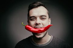 Man holding chili pepper in his teeth. Funny guy eating hot, spicy pepper on a gray background. Health concept. Stock Photos