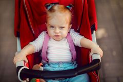 Expressive girl in carriage. Adorable little girl sitting and riding in baby carriage on the street royalty free stock images