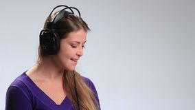 Expressive girl in headphones enjoying music stock video footage