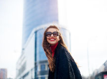 Expressive girl with long hair having fun in city.She wears sunglasses and smiling to camera with snow-white smile. Stock Photos