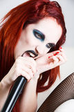 Expressive gothic woman with artistic makeup. Studio shot of expressive gothic red haired woman with artistic makeup screaming to the microphone over white royalty free stock photo