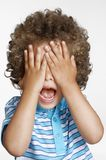 Expressive kid. Expressive surprised kid covering his eyes Royalty Free Stock Image
