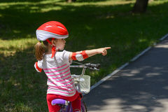 Expressive little girl with colorful red safety helmet riding a bicycle. Adorable girl with colourful red safety helmet, riding a bike on beautiful autumn day Stock Photos