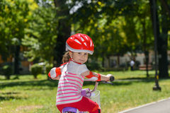 Expressive little girl with colorful red safety helmet riding a bicycle Royalty Free Stock Images