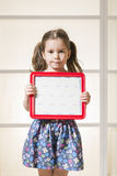 Expressive little girl holding a blank magnetic board. Beautiful child showing blank area for sign or copy space Royalty Free Stock Photography