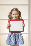 Expressive little girl holding a blank magnetic board. Beautiful child showing blank area for sign or copy space Royalty Free Stock Image