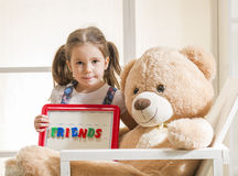 Expressive little girl holding a magnetic board. Happy little girl sitting in Teddy bear arms holding magnetic board with colored magneticletters written friends Royalty Free Stock Photos