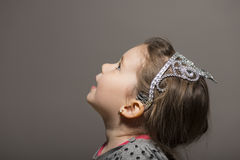 Expressive little girl. Lovely expressive little girl wearing silver princess crown looking up, studio shot on gray background Stock Photos