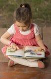 Expressive little girl reading loud Stock Photos