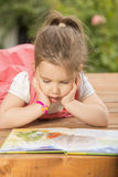 Expressive little girl reading loud Stock Photography