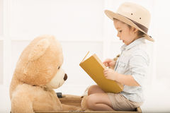 Expressive little girl reading to her teddy bear Royalty Free Stock Photos