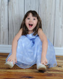 Expressive little girl sitting on floor. Expressive little girl in dress sitting on floor with eyes and mouth wide open stock images