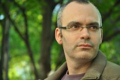 Expressive look. Man with intense, wondering expression, looking in the horizon with a reflective attitude. He is wearing reading glasses and behind him there's Stock Photography