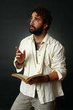 Expressive man gesturing with book Stock Photography