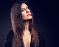 Expressive model posing in black jacket with long straight hair. Style and long neck on dark background. Closeup fashion portrait. Toned royalty free stock photo