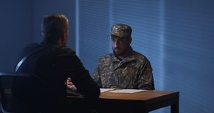 Expressive policeman examining military man in interview room. Policeman laying few papers on table in front of detained suspect men in military uniform and royalty free stock photos